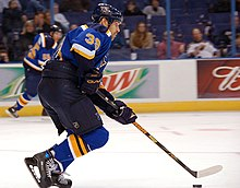 An ice hockey player skates on the ice with his stick and the puck. He is wearing a blue jersey and black pants.