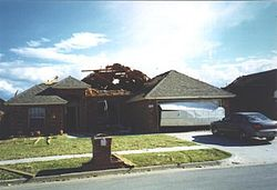 An example of EF1 damage. Here, the roof has been substantially damaged, and the garage door blown outwards, but the walls and supporting structures are still intact.