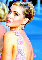 A young blonde woman with her hair tied up at the back, wearing diamond earrings and a pink flowery dress, photographed from behind and to the left and looking sideways from the viewer