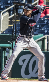A baseball player in a navy jersey and gray pants