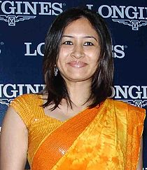 A woman in yellowish-orange saree, cut-sleeves blouse, open hair and smiling face