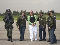"A handcuffed man in a light green T-shirt, flak jacket and white pants being escorted by two men on either side in green jackets and caps with the Spanish word ""Policia"" identifying them as police officers. To the left is a soldier in body armor and helmet, carrying an assault rifle. At the right is another police officer, his back to the camera, slightly obscuring another similarly equipped soldier."