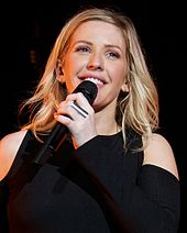 A smiling blonde woman with a black top holding a microphone.
