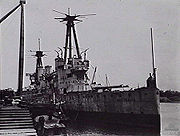 A World War I-era warship tied up to a dock. The ship is in poor condition, and has streaks of rust on her hull.