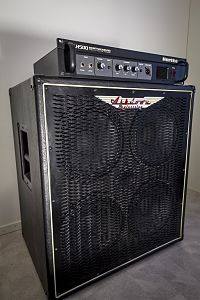 An amplifier unit sitting on top of a bass speaker cabinet. The speaker has four ten-inch loudspeakers.