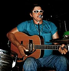 Adkins playing guitar, singing, surrounded by his drumkit