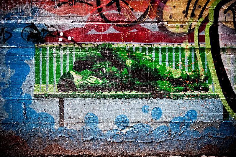 File:Homeless on bench stencil Melbourne.jpg