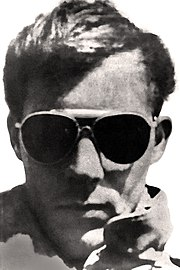 Photograph showing just the head of a man with a serious expression, aviator sunglasses, a full head of medium-short hair, and a visible collar of a leather jacket
