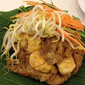 Tahu goreng - Indonesia Tahu goreng and omelette arranged on a plate garnished with bean sprouts, cucumber and carrot