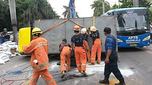 Traffic collision - A rolled over box truck being handled by fire fighters in Jakarta, Indonesia