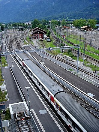 Interlaken Ost railway station - The station looking east. The standard gauge Thunersee line platforms are nearest the camera, and run beyond the station into turnback sidings. To the right of this, the line to Bönigen can be seen curving rightwards. On the other side of the depot building, the metre gauge Brünig can be seen climbing and curving left, in order to pass over the Bönigen line and the Aar river. The BOB lines are out of shot to the right.