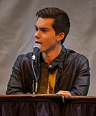 The image is of a young man talking into a microphone