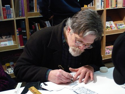 Photo of a bearded and bespectacled man drawing