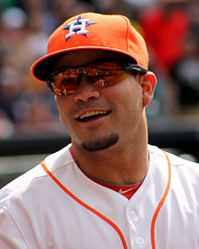 "A man in a white baseball wearing and orange baseball cap with an ""H-star"" logo smiles."