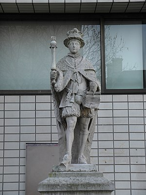 A stone statue of Edward VI. Edward wears a crown and holds a parchment in his left hand and a sceptre in his right hand. The king stands on a stone plinth.