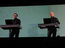 Kraftwerk performing onstage, standing on two separate dais.