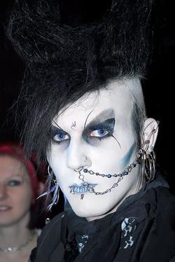 Goth im Grufti-Look, mit toupierten Haaren, Piercings, Rosenkranz und alchemistischem Symbol auf der Stirn