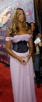A woman is standing up. She is wearing a long pink dress with a black corset. She is holding her hands in front of her body.