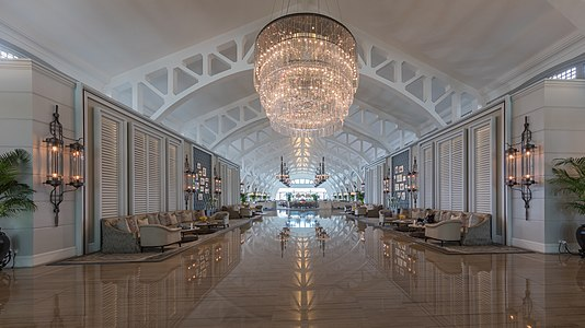 Symmetric view of the spacious lobby hall with couches and giant chandelier reflecting on the floor at The Fullerton Bay Hotel, Singapore