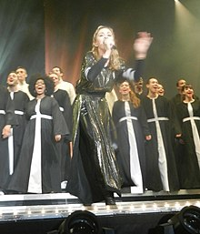 Madonna in the middle of a stage singing as a choir is present behind her.