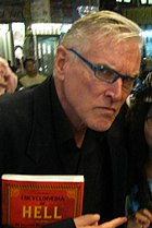 A man is holding a book and humorously glaring at the camera