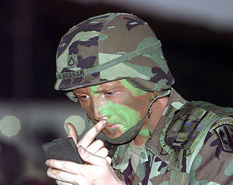 Camouflage - A soldier applying camouflage face paint; both helmet and jacket are disruptively patterned.