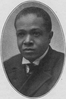 McCants Stewart, a young clean-shaven African American man wearing a double breasted suit with a white shirt with wing collar and tie