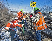 "Four men in reflectorized orange vests and neon green helmets standing next to a set of four railroad tracks installing a signpost next to the track. One is holding a sign with the letters ""SR"" in black on yellow. The ground, covered with a thin snow, slopes steeply to the left and an overhead gantry for the catenary is in the background."