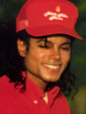 A headshot of a man wearing a red baseball cap and shirt. He has long black hair and is smiling towards the camera.