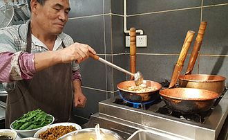 Yunnan cuisine - Mixian (rice noodles) being cooked in copper pots on gas stoves at a restaurant in Kunming.