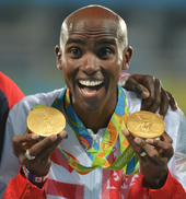 Mo Farah holding up two gold medals