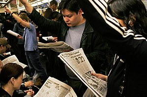 Media in New York City - Straphangers use newspapers on New York's mass transit system.