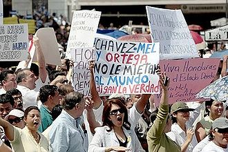 Chronology of the 2009 Honduran constitutional crisis - Anti-Zelaya demonstrators; one holds a sign warning against Hugo Chávez, Zelaya and Daniel Ortega