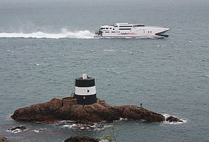 Transport in Jersey - A Condor Ferries catamaran heading west around Jersey past La Tour de Vinde, Noirmont, Saint Brelade