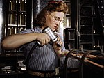 Operating a hand drill at North American Aviation, Inc, a woman is working in the control surface department assembling a section of the leading edge for the horizontal stabilizer of a plane, Inglewood, Calif (cropped).jpg
