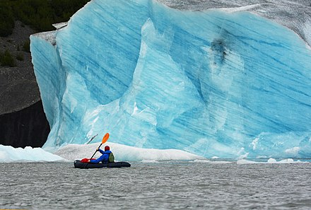 A packrafter passes a wall of freshly exposed blue ice on Spencer Glacier, in Alaska. Glacial ice acts like a filter on light, and the more time light can spend traveling through ice, the bluer it becomes. Packrafting at Spencer Glacier. Chugach National Forest, Alaska.jpg
