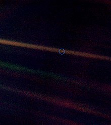 A tiny, pale blue dot is contrasted against the vastness of space