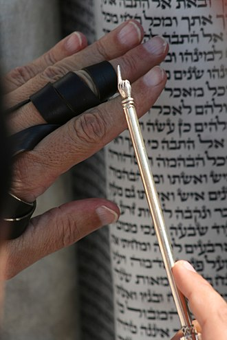 Yad - Pointing with a yad on an open Torah scroll.