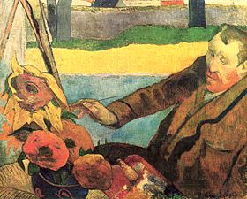 A seated red bearded man wearing a brown coat; facing to the left; with a paint brush in his right hand, is painting a picture of large sunflowers