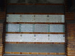 Memorial tablets arranged in three rows on a wall. Those in the centre are in the green and white Arts and Crafts Movement style, while those above and below are in the more recent design. There are empty rows above and below the three filled rows.
