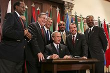 Rangel and six other men stand around a table, where President George W. Bush signs a bill