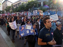 "People peacefully marching up a street. Several are carrying signs displaying pro-same-sex marriage slogans, such as ""We all deserve the freedom to marry."" Most people have sad or serious facial expressions."
