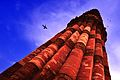 Qutab Minar from bottom with an airplane flying overhead.jpg