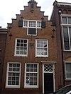 foto van Huis met trapgevel met sierankers en wapensteen. Gerestaureerd