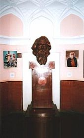 A bronze bust of a middle-aged and forward-gazing bearded man supported on a tall rectangular wooden pedestal above a larger plinth set amidst a small ornate octagonal museum room with pink walls and wooden panelling; flanking the bust on the wall behind are two paintings of Tagore: to the left, a costumed youth acting a drama scene; to the right, a portrait showing an aged man with a large white beard clad in black and red robes.