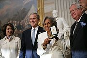 Black woman holding aloft award presented by President George W. Bush and two other dignitaries