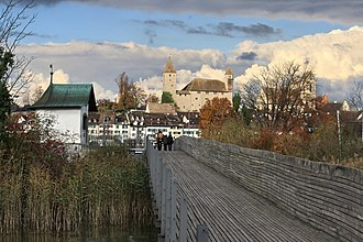 Holzbrücke Rapperswil-Hurden - The wooden bridge, Seedamm to the left, Heilig Hüsli and Rapperswil respectively Rapperswil Castle and Stadtpfarrkirche Rapperswil (to the right) in the background