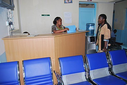 Receptionist attending to an outpatient Receptionist attending to clients at the out patient.JPG