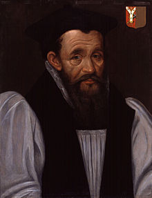 A head-and-shoulders portrait of Richard Bancroft. The portrait portrays Bancroft on a grey background, wearing a white shirt with a black vest. Bancroft is wearing a black cap and has collar length brown hair. Over Bancroft's left shoulder is a red and brown family crest