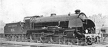 Side-and-front view of a 4-6-0 locomotive on an turntable. A member of the crew is standing next to the front.